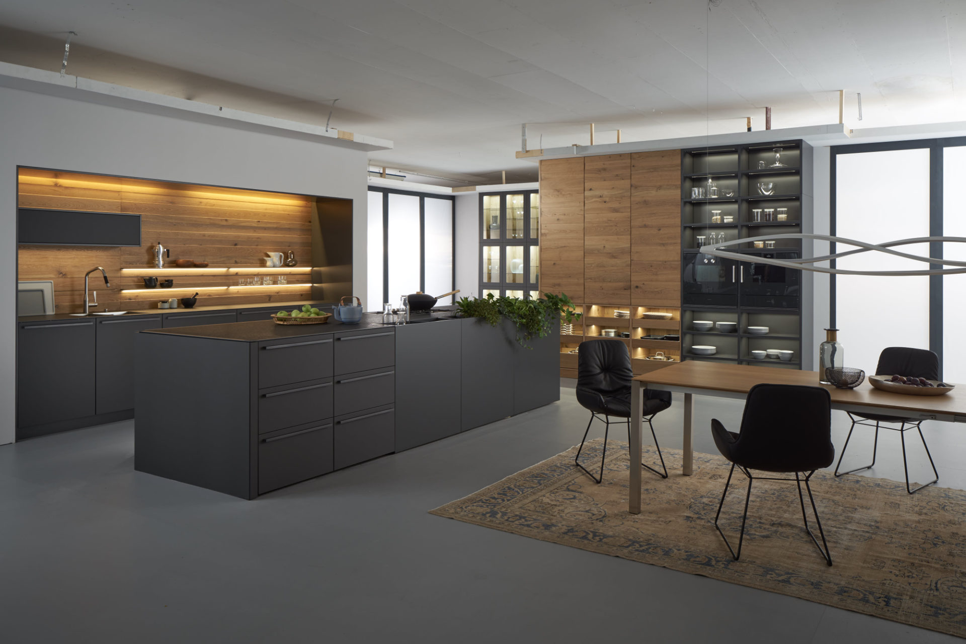 This modern kitchen by German supplier, Leicht features their BONDI-E matt lacquered doors in 'Carbon Grey', paired with VALAIS in 'Alpine natural oak' veneer.