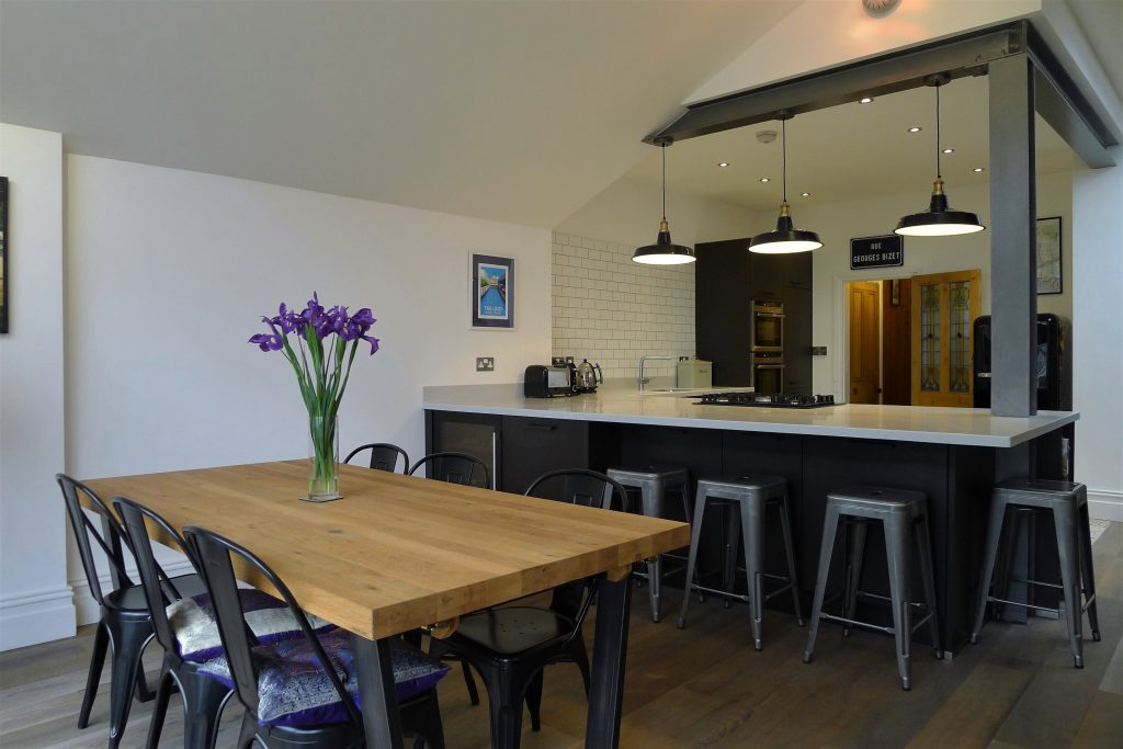 Side Shot of Kitchen with Exposed Steel Work and Matching Grey Chairs